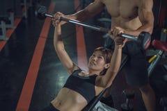 Imprensa de banco de ajuda da mulher do instrutor pessoal no gym, treinamento com barbell, mulher de ajuda do instrutor pessoal q fotografia de stock