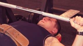 Imprensa de banco do homem O barbell de encontro do homem pressiona no gym, no banco O indivíduo esteve no gym vídeos de arquivo