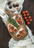 Imprensa o brushtta com os tomates de cereja roasted, queijo macio Fotos de Stock Royalty Free