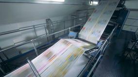 Imprenta y balanceo coloreado del papel a través de una máquina almacen de metraje de vídeo
