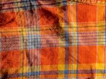 Impresión anaranjada y amarilla de la tela escocesa como fondo Modelo simétrico del Rhombus fotografía de archivo