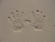 Impresión de la mano en la playa arenosa Imagen de archivo libre de regalías
