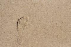 Impresión del pie desnudo en la arena blanca Impresión descalza de la hembra en la arena de la playa Fotografía de archivo
