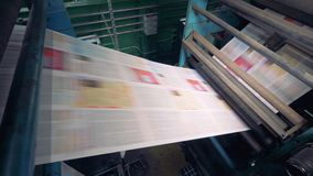 Impresión en una planta, cierre del periódico para arriba Periódico impreso en una máquina de la casa de impresión