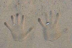 Impresiones de la mano con las alianzas de boda en la arena de la playa Fotos de archivo libres de regalías