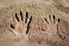 Impresiones de la mano en la arena Imagenes de archivo