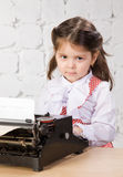 Impresiones de la niña en la máquina de escribir antigua Imágenes de archivo libres de regalías