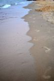 Impresiones del pie en arena Imagen de archivo