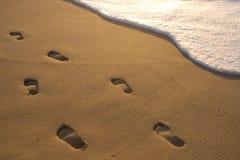 Impresiones del pie en la arena Imagen de archivo