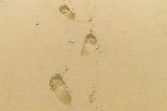 Impresiones del pie en la arena Imágenes de archivo libres de regalías