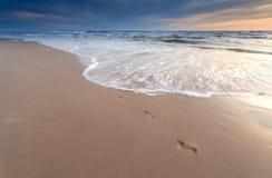 Impresiones del pie en la playa de la arena en la puesta del sol Imagenes de archivo