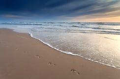 Impresiones del pie en la playa de la arena en la puesta del sol fotos de archivo libres de regalías