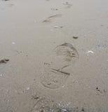 Impresiones del pie en una playa arenosa Imagen de archivo libre de regalías