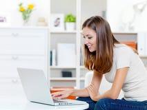 Impresiones sonrientes de la mujer en la computadora portátil Foto de archivo