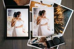 Impreso casandose las fotos con la novia, una cámara del negro del vintage y una tableta negra con una imagen de la novia fotos de archivo libres de regalías