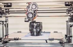 impresora 3D que imprime un modelo bajo la forma de primer negro del cráneo foto de archivo