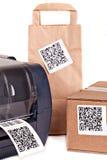 Impresora del código de barras y cajas de empaquetado marcadas con un código de barras Imagen de archivo libre de regalías