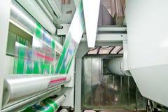 Impresora industrial del rotograbado con la tinta y los carretes de película plásticos que corren en fábrica foto de archivo