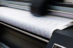 Impressão industrial no material tecido; a impressora a jato de tinta digital moderna põe uma imagem azul do teste padrão sobre u fotografia de stock