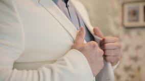 Impressario som får klar för ett jobb och att sätta hans vita dräkt Närbildsikt av manliga händer som bär omslaget som får klädd lager videofilmer