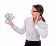 Impressed brunette woman holding dollar bills. Impressed brunette businesswoman holding dollar bills with an excited gesture of one hand and smiling while Stock Photos