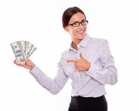 Impressed brunette woman holding dollar bills. Impressed brunette businesswoman holding dollar bills with an excited gesture pointing at the money while smiling Royalty Free Stock Images