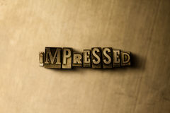 IMPRESSED - close-up of grungy vintage typeset word on metal backdrop Royalty Free Stock Image