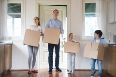 Impressed family carrying boxes moving in to new house. Happy family of four carry boxes entering new house, impressed parents and kids bring in cardboard royalty free stock photos