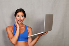 Impressed lady with hand on face and toothy smile. While holding laptop in fitness gym clothing on grey texture background royalty free stock photo