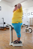 Impressed overweight woman on scales in gym. Impressed overweight woman standing on scales in the gym stock photography