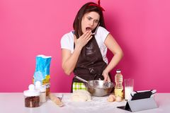 Impressed surprised emotional model poses isolated over pink background, wearing brown apron and white t shirt , talking over her. Mobile phone, looks shocked royalty free stock photography