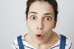 Impressed and surprised woman with pierced nose, looking up at camera with widened eyes and opened mouth, being shocked. Over gray background. Girl is stunned royalty free stock photography