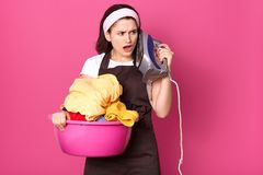 Impressed tired housewife standing isolated over pink background in studio, holding basin with clothes and iron, touching face royalty free stock photography