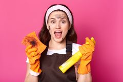 Impressed tired model posing isolated over pink background in studio, opening mouth with shock, doing household chores, wearing. Brown apron, t shirt and white royalty free stock images