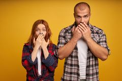 Impressed two young attractive female and male loose speech from fright, cover mouthes with both palms, being shocked by negative stock photo