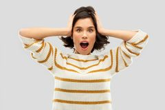 Impressed woman in pullover holding to her head. Emotion, expression and people concept - happy impressed young woman in striped pullover holding to her head royalty free stock photos