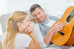 Impressing girl by playing guitar Stock Image