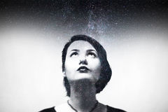 Impression portrait of young girl composition with night sky. Multi exsposure portrait. Woman look up out of frame frame. Black and white image Stock Images
