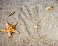 Impressions de main dans le sable Photo stock