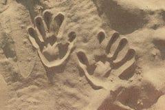 Impressions de main dans le sable image stock