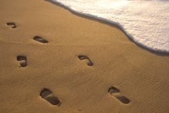 Impressions de pied dans le sable Image stock