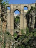 Bridge across the gorge at Ronda, Andalucia, Spain. Impressive arched bridge across the gorge at Ronda against a blue sky with buildings visible through the royalty free stock images