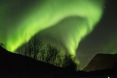 NORTHERN LIGHTS ARC IN THE ARCTIC SKY. Impressive Aurora Borealis in the Arctic sky Royalty Free Stock Images