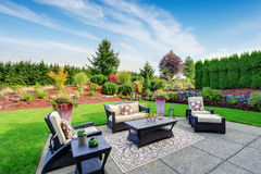 Impressive backyard landscape design with patio area. Impressive backyard landscape design. Cozy patio area with settees and table Royalty Free Stock Image