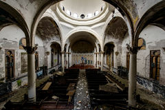Impressive Center Dome with Overturned Pews & Garbage in Sanctuary - Abandoned Church. An impressive center dome rests above overturned pews and garbage in the royalty free stock photos