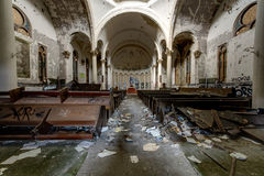 Impressive Center Dome with Overturned Pews & Garbage in Sanctuary - Abandoned Church. An impressive center dome rests above overturned pews and garbage in the stock images