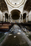 Impressive Center Dome with Overturned Pews & Garbage in Sanctuary - Abandoned Church. An impressive center dome rests above overturned pews and garbage in the stock photography