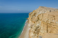 Impressive cliffs with turquoise ocean at the coast at Caotinha, Angola. The yellow sandstone drops sharply down to the sea here Stock Image