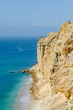 Impressive cliffs with turquoise ocean at the coast at Caotinha, Angola. The yellow sandstone drops sharply down to the sea here Royalty Free Stock Images