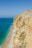 Impressive cliffs with turquoise ocean at the coast at Caotinha, Angola. The yellow sandstone drops sharply down to the sea here Stock Images